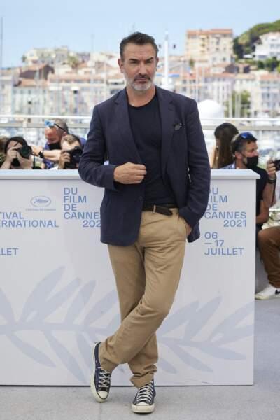 Jean Dujardin prend une pose sérieuse devant le parterre de photographe au Festival de Cannes, le 17 juillet