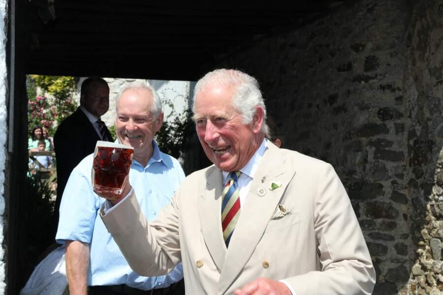 Le prince Charles, joyeux et décontracté, trinque avec les locaux lors de son passage dans un pub d'Iddesleigh, ce 21 juillet 2021.