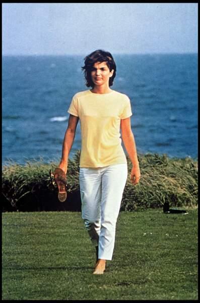 Jackie Kennedy élégante et estivale en pantalon blanc et haut flashy