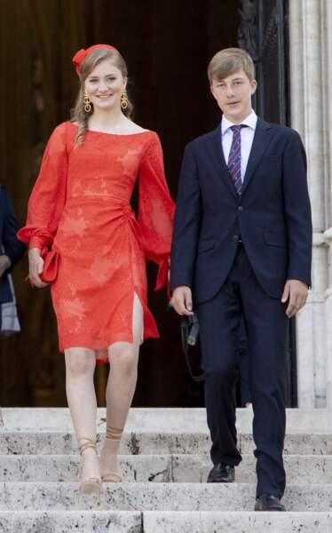 Sa robe rouge était rehaussée d'une dentelle florale ton sur ton.