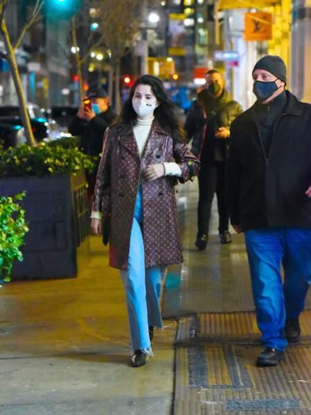Selena Gomez en 2021 : Casual et classe elle sort le trench-coat à monogramme Louis Vuitton, associé à un col roulé blanc, un jean taille haute et des bottes noires