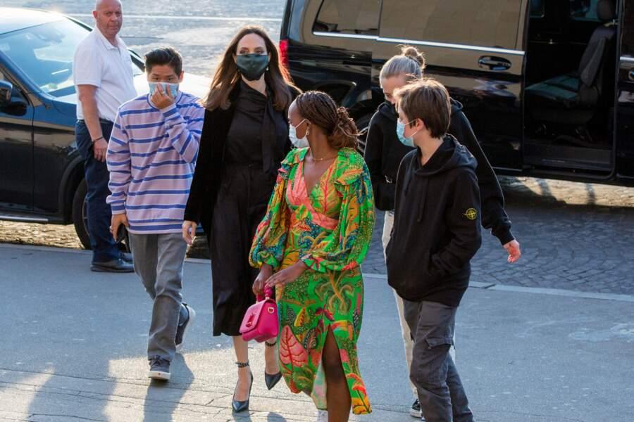 Zahara Jolie-Pitt a opté pour une longue robe bigarrée avec un sac rose fluo griffé Louis Vuitton, pour se rendre en famille au restaurant La Girafe, à Paris, ce jeudi 22 juillet 2021