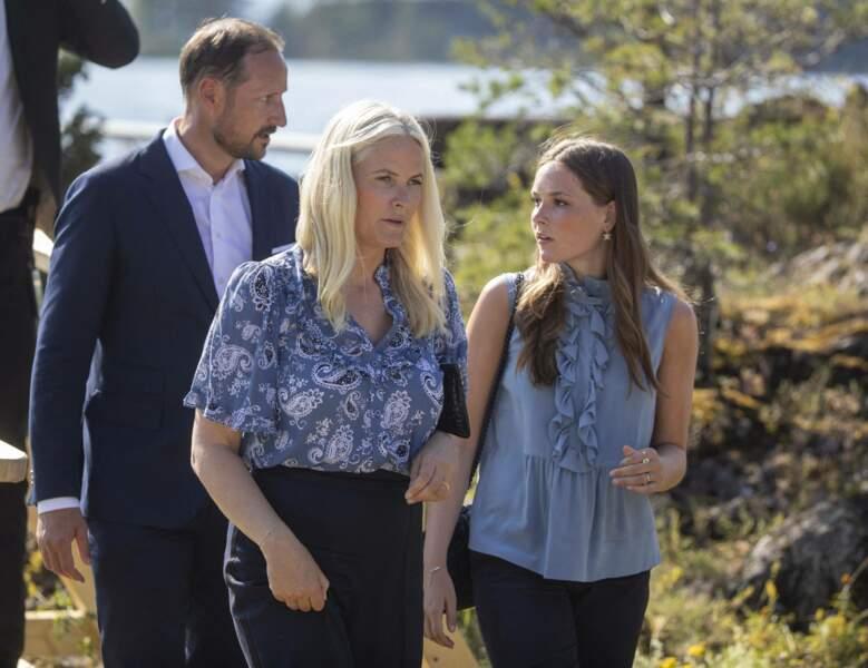 Accompagnée de sa fille,  la princesse Ingrid Alexandra de Norvège, Mette-Marit met en valeur sa chevelure blonde polaire avec un chemisier bleu électrique à Oslo, le 22 juillet 2021.