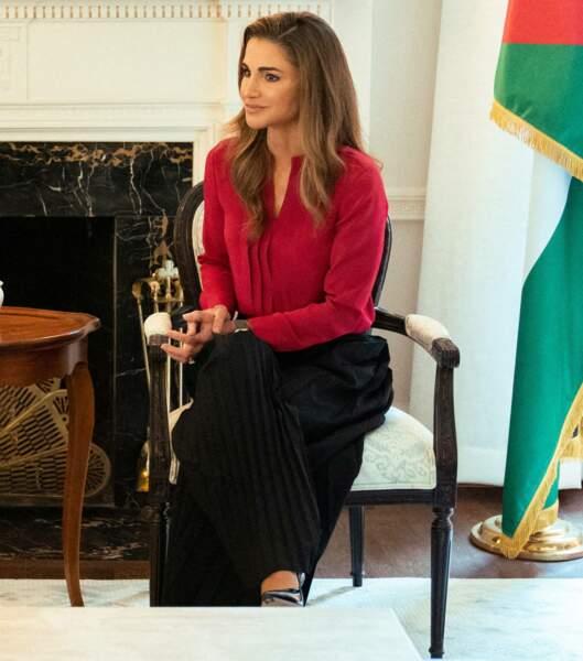 Rania de Jordanie portait un chemisier écarlate avec un pantalon fluide noir.
