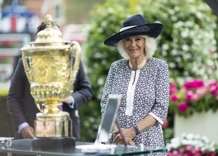 La duchesse de Cornouailles admire le trophée du King George Diamond Weekend dans son élégante robe fleurie.