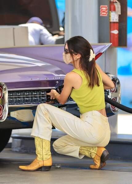 Kendall Jenner porte un pantalon taille haute couleur crème, une paire de santiags et même une pince crabe dans une station essence à Malibu