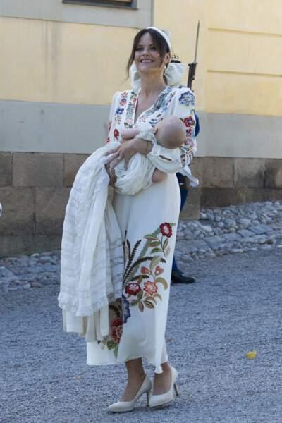 Son nom a été brodé sur un pan de cette robe, aux côtés des prénoms de tous les autres membres de la famille qui l'ont portée.