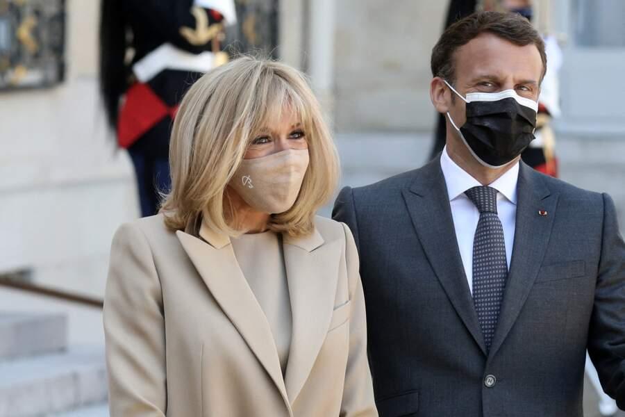 Brigitte Macron porte très souvent un masque de couleur nude, coordonné à sa robe et son manteau, ici à l'Elysée le 26 avril 2021.
