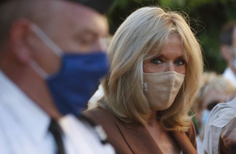 Brigitte Macron avec un masque nude de la marque Bettimask assorti à sa veste le 17 août 2021
