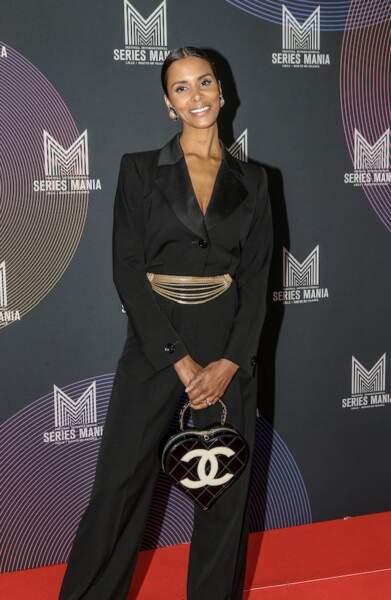 Shy'm, très souriante en costume en satin noir et sac vintage Chanel