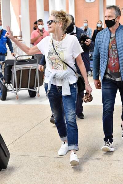 Sharon Stone a choisi un look rock avec un pull en laine noué à sa taille et des baskets blanches