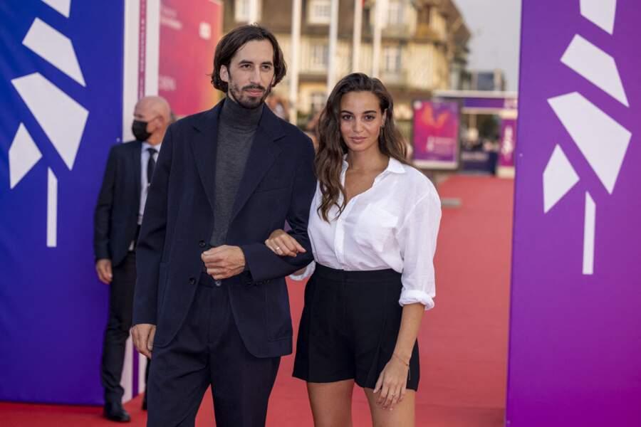 L'artiste Antoine Lomepal et l'actrice Souheila Yacoub sur le tapis rouge de Deauville, bras dessus bras dessous.