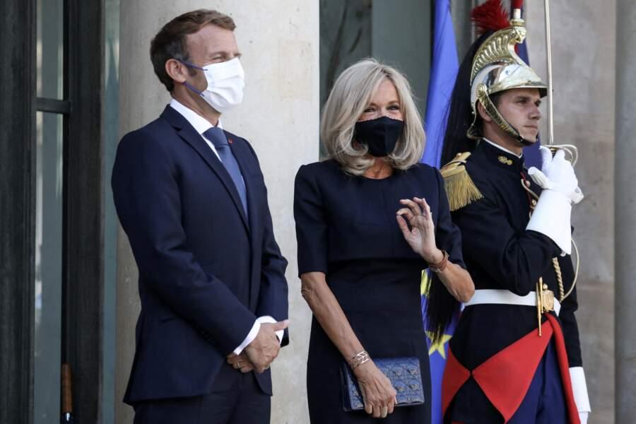 Brigitte Macron et l'art de l'accessoire : une pochette, sa montre fétiche, sa manchette et une bague.