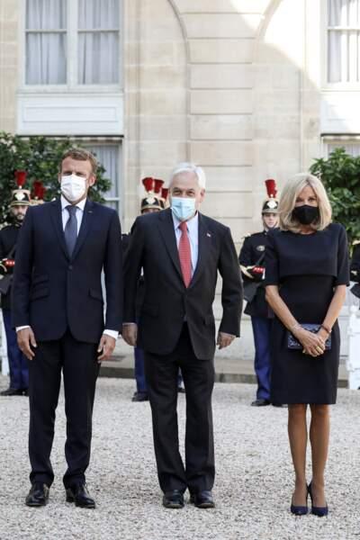 Brigitte Macron en robe droite qui arrive juste au-dessus du genou et escarpins noirs.