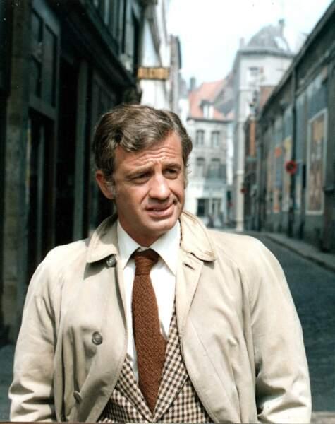 """Jean-Paul Belmondo, en trench et veste à carreaux, sur le tournage du film """"Le corps de mon ennemi"""". 1976"""
