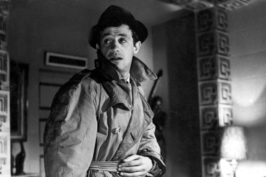 """Jean-Paul Belmondo sur le tournage du film """"Le doulos"""" en 1962 dans son trench ceinturé et son chapeau."""