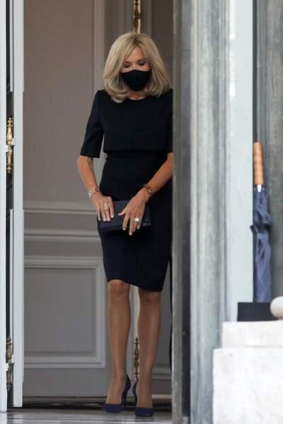 Brigitte Macron très chic et sobre en robe noire, escarpins noirs et sac à main noir, jusqu'au masque assorti.