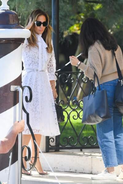 Jennifer Lopez très élégante en robe midi en dentelle, lunettes de soleil xxl et escarpins noirs.