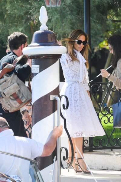 Jennifer Lopez a choisi une très belle robe midi blanche en dentelle signée Valentino et une paire d'escarpins à talons hauts.