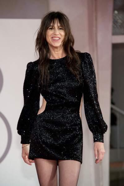 Charlotte Gainsbourg, rayonnante, les cheveux longs et une robe courte noire et strassée signée Saint-Laurent Paris