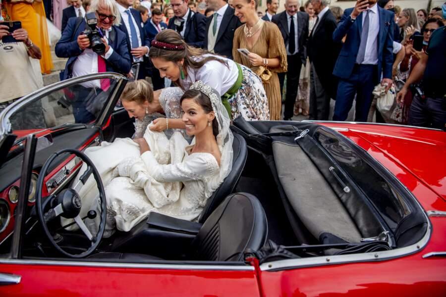 Le départ des mariés dans une sublime voiture rouge.