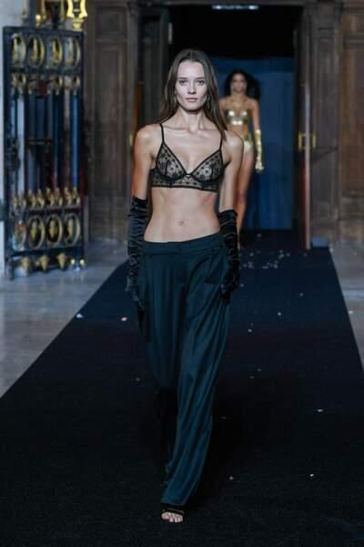 Alicja Tubilewicz porte un soutien-gorge triangle noir sur pantalon large et gants Opéra au défilé Etam 2021