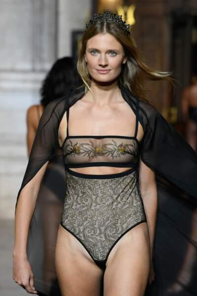 Constance Jablonski, égérie Etam, porte un body ajouré brodé et une cape/pardessus transparente pour le défilé Etam 2021
