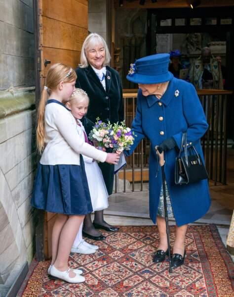 Une enfant de chœur a offert une bouquet de fleurs à la reine Elizabeth II après le service d'action de grâce donné en l'abbaye de Westminster pour marquer le centenaire de la Royal British Legion, à Londres, le 12 octobre 2021.
