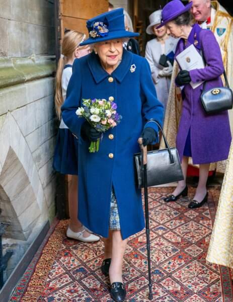 La reine Elizabeth II avec son bouquet de fleurs et sa canne pour l'aider à marcher à la sortie de l'abbaye de Westminster, à Londres, le 12 octobre 2021.